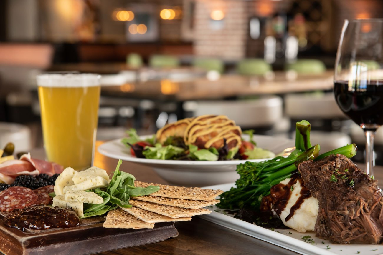 Meat and cheese board, braised short rib and broccolini and crab cakes with a glass of beer and a glass of red wine