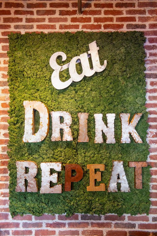 Wall décor at The Met Kitchen with lettering Eat, Drink, Repeat
